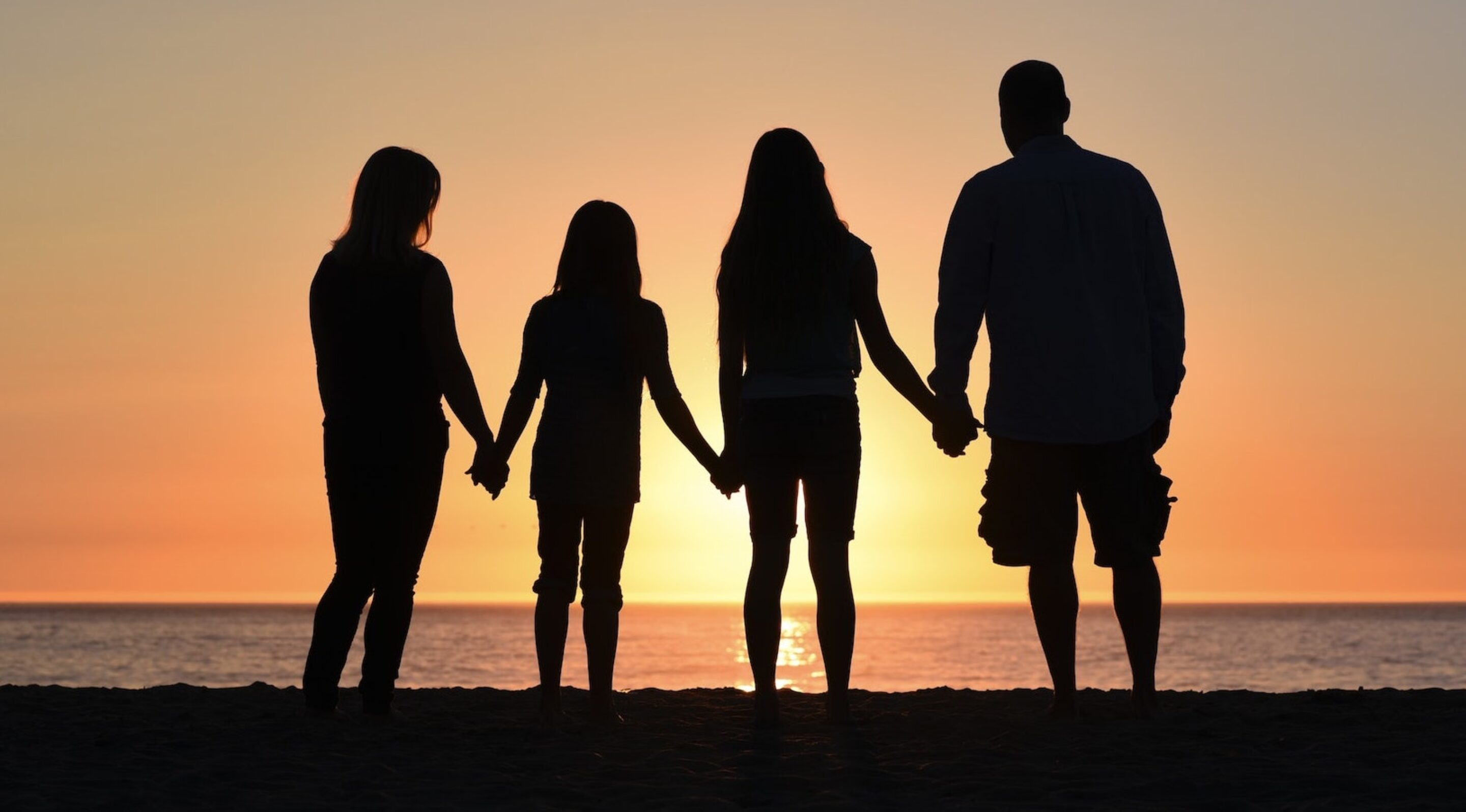 Silhouette of a family on a beach at sunset